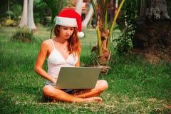 A jovem senhora está sentando-se na grama com um portátil em um chapéu do Natal Fotos de Stock