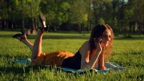 Jovem senhora feliz que encontra-se no gramado verde e que fala no smartphone vídeos de arquivo