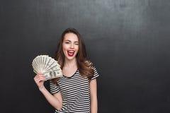 Jovem senhora feliz que está sobre a parede cinzenta e que guarda o dinheiro Fotografia de Stock