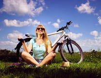 Jovem senhora feliz que relaxa em um prado verde após a ciclagem imagens de stock royalty free