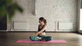 A jovem senhora na roupa na moda dos esportes está fazendo as torções do corpo que sentam-se na posição dos lótus sobre a esteira vídeos de arquivo