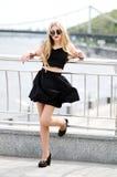Jovem senhora na saia do bkack, na camisa sem mangas e na sapata alto-colocada saltos Imagens de Stock Royalty Free