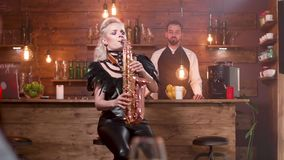 A jovem senhora no traje preto 'sexy' da fase executa uma música em um saxofone vídeos de arquivo