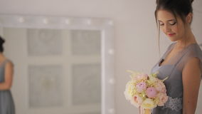 A jovem senhora no vestido cinzento com ramalhete está na frente do espelho video estoque