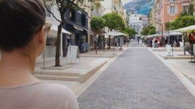 Jovem senhora que anda ao longo da rua com as lojas, procurando vendas, cidade europeia video estoque