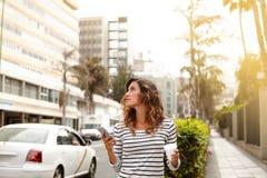 Jovem senhora que anda na rua da cidade e que olha afastado Imagens de Stock Royalty Free