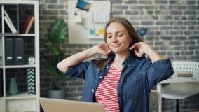 Jovem senhora que datilografa no trabalho usando o portátil que senta-se então para trás na cadeira confortável vídeos de arquivo