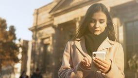 Jovem senhora que enrola depositando o app no smartphone perto da construção clássica bonita filme