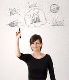 Jovem senhora que esboça ícones e símbolos financeiros da carta Fotografia de Stock