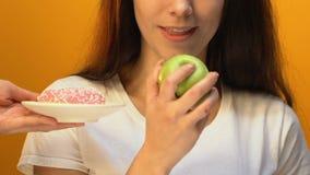 Jovem senhora que escolhe a maçã verde em vez da filhós doce, apreciando o fruto suculento vídeos de arquivo