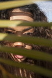 Jovem senhora que esconde em choque atrás das folhas Fotos de Stock Royalty Free