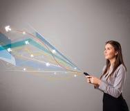 Jovem senhora que está e que guarda um telefone com linhas e as setas abstratas coloridas Imagem de Stock