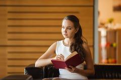 Jovem senhora que faz anotações no diário vermelho Mulher no planeamento branco do vestido Fotos de Stock Royalty Free