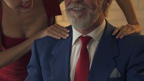 Jovem senhora que faz massagens ombros ao homem rico idoso, tentando seduzir e manipular vídeos de arquivo