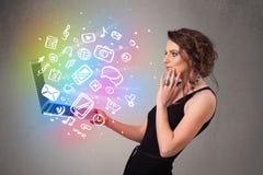 Jovem senhora que guarda o caderno com mão colorida ícones tirados dos multimédios Fotografia de Stock