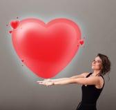 Jovem senhora que guarda o coração bonito do vermelho 3d Imagens de Stock