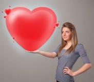 Jovem senhora que guarda o coração bonito do vermelho 3d Fotografia de Stock Royalty Free