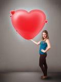 Jovem senhora que guarda o coração bonito do vermelho 3d Foto de Stock Royalty Free
