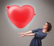 Jovem senhora que guarda o coração bonito do vermelho 3d Imagem de Stock Royalty Free