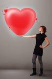 Jovem senhora que guardara o coração bonito do vermelho 3d Imagens de Stock