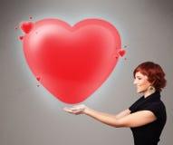 Jovem senhora que guardara o coração bonito do vermelho 3d Imagens de Stock Royalty Free