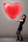 Jovem senhora que guardara o coração bonito do vermelho 3d Fotografia de Stock Royalty Free