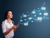 Jovem senhora que guardara um telefone com setas e ícones da mensagem Imagens de Stock Royalty Free