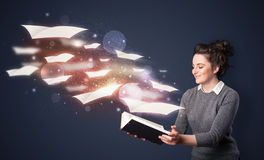 Jovem senhora que lê um livro com as folhas de voo que saem do b foto de stock royalty free
