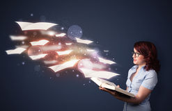 Jovem senhora que lê um livro com as folhas de voo que saem do b imagem de stock royalty free