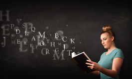 Jovem senhora que lê um livro com letras do alfabeto imagem de stock