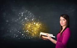 Jovem senhora que lê um livro mágico Imagens de Stock Royalty Free