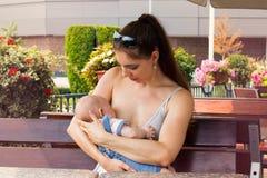 A jovem senhora que nutre seu bebê bonito, mamã bonita é com o bebê recém-nascido exterior e que amamenta em público, sentando-se foto de stock royalty free