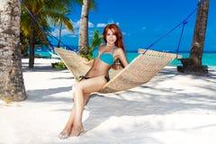 Jovem senhora que relaxa na rede na praia tropical foto de stock