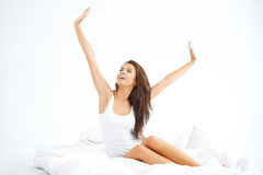 Jovem senhora que senta-se na cama e no esticão Fotografia de Stock Royalty Free