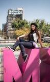 Jovem senhora que senta-se na escultura de CDMX no la Condesa fotografia de stock royalty free
