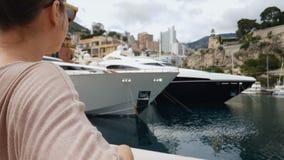A jovem senhora que senta-se no banco perto do mar, olhando os iate estacionados no cais, relaxa video estoque