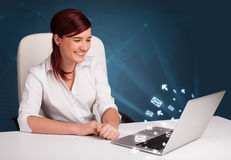 Jovem senhora que senta-se no dest e que datilografa no portátil com ico da mensagem Fotografia de Stock Royalty Free
