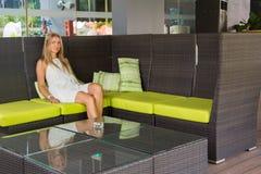 Jovem senhora que senta-se no sofá moderno vestir da tabela foto de stock royalty free