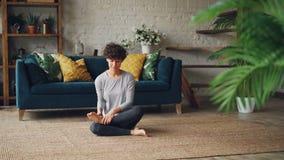 A jovem senhora relaxado está sentando-se no agnistambhasana da pose do log do fogo no assoalho do apartamento e está respirando- vídeos de arquivo