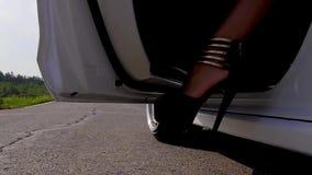 A jovem senhora sai do carro Mulher que sai do carro Feche acima na porta de carro e no pé da menina Vestir do pé da mulher filme