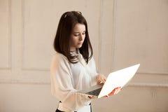 A jovem senhora trabalha no portátil Imagens de Stock Royalty Free