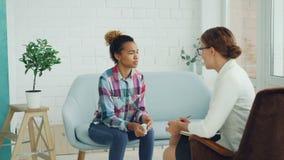 A jovem senhora virada na roupa ocasional está tendo a sessão de terapia com o psicólogo no estúdio claro A menina está falando e filme
