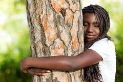 Joven africano con las trenzas que abraza el árbol Fotografía de archivo libre de regalías