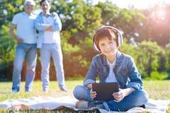 Joven alegre que escucha la música al aire libre Foto de archivo