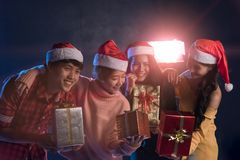 Joven asiático del grupo divirtiéndose en el partido del ` s del Año Nuevo, sosteniendo el regalo B Foto de archivo