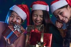 Joven asiático del grupo divirtiéndose en el partido del ` s del Año Nuevo, sosteniendo el regalo B Fotografía de archivo