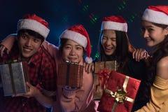 Joven asiático del grupo divirtiéndose en el partido del ` s del Año Nuevo, sosteniendo el regalo B Fotos de archivo