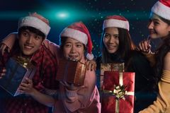Joven asiático del grupo divirtiéndose en el partido del ` s del Año Nuevo, sosteniendo el regalo B Imágenes de archivo libres de regalías