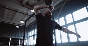 Joven atlético barbudo hombre caucásico durante ejercicio funcional extremo levantando el timbre en un gran gimnasio a cámara l metrajes