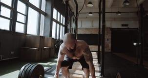 Joven atlético barbudo hombre caucásico levantando pesada barba en un gran gimnasio duro. Poder y concepto de la fuerza metrajes